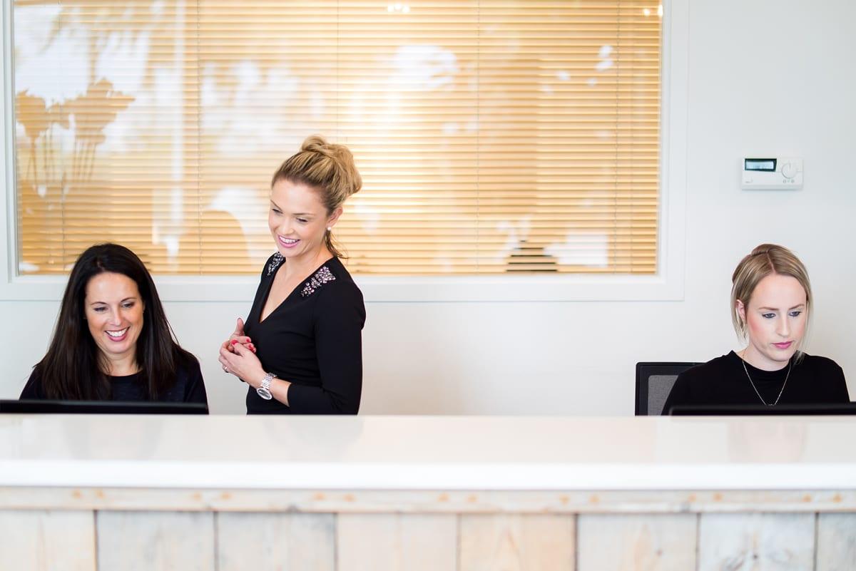 Drie receptionistes achter de balie